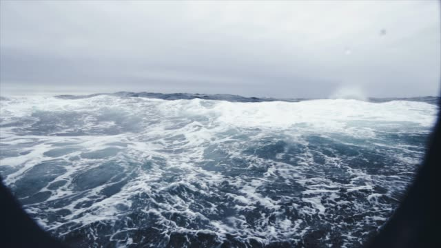 from the porthole window of a vessel in a rough sea - natante industriale video stock e b–roll