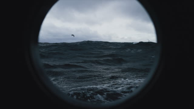 vídeos de stock e filmes b-roll de from the porthole window of a vessel in a stormy sea - navio