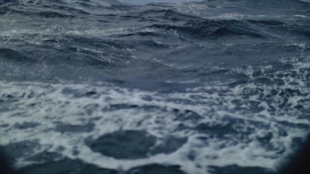 vídeos de stock e filmes b-roll de from the porthole window of a vessel in a stormy sea - maré