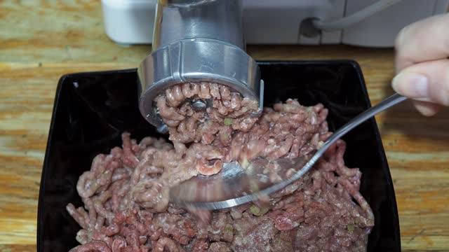 front and above view of grinding of minced meat and onion front and above view of grinding of minced meat and onion in electric meat grinder and cleaning grid by spoon during grinding on wooden table at home kitchen ground beef stock videos & royalty-free footage