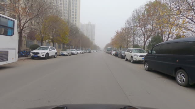 pov: front car driving on the city road during winter and gray pollution day. beijing. china - segnale per macchine e pedoni video stock e b–roll