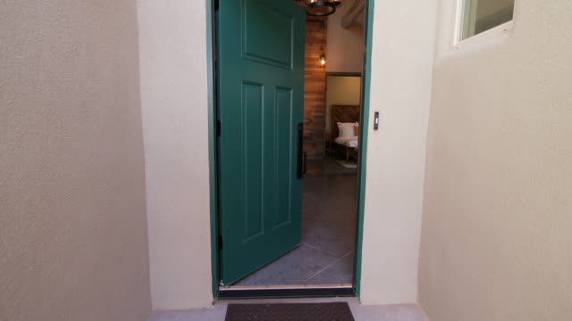 Front Door Opening on Southwest Home Reveal Interior shot rises on a front entrance of a home in the southwest style home. Door opens revealing front entrance to home facade stock videos & royalty-free footage
