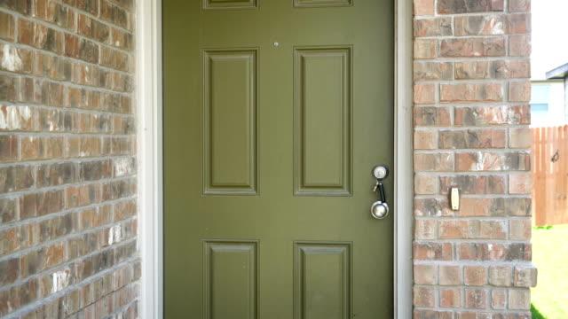 Front Door patio with Keys in door Front Door patio with Keys in door , silver door knob and brick walls on brick home front door stock videos & royalty-free footage