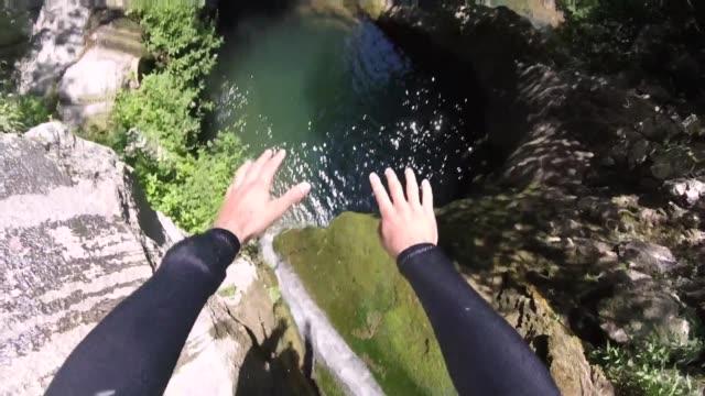 Front flip jump into water in a canyon