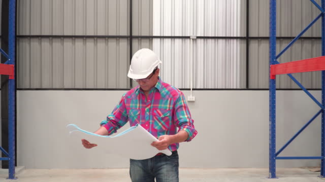 front following view: Asian man engineer looking at blueprint for checking shelf and building in Warehouse