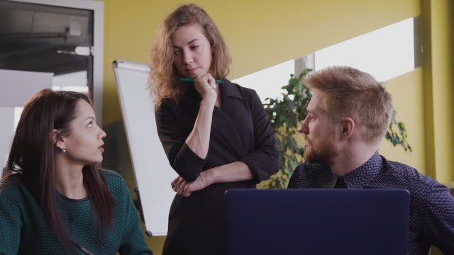 Front of Group of colleagues discussing project ideas in modern office at table