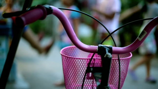front of the bike's Video close up and depth of field, The front of the bike's pink And with the background blurred by a group of children were playing,still shot. handle stock videos & royalty-free footage