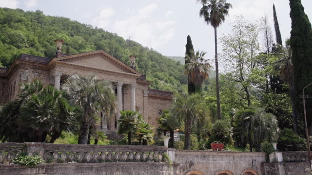 front part of old medieval castle exterior with palm garden - balaustrata video stock e b–roll