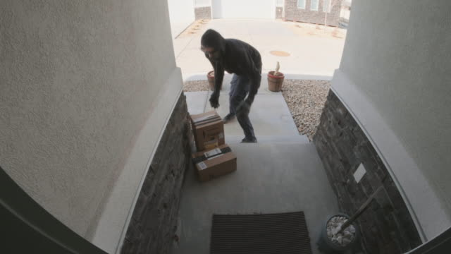 Front Porch Security Camera Home Front Porch Burglary A hooded man burglarizing a front porch of a residential home during the daytime. View from a doorbell surveillance security camera at the house. porch stock videos & royalty-free footage
