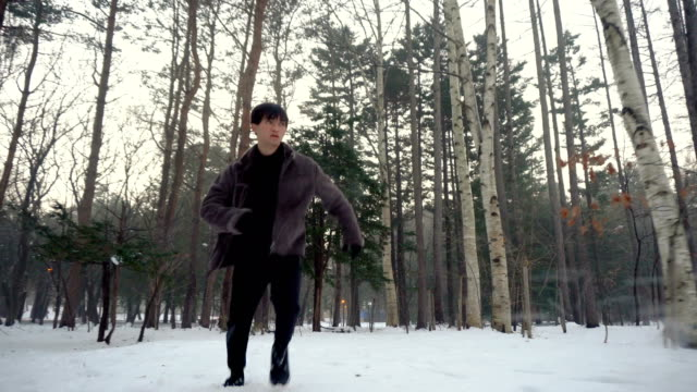 Front Tracking Shot - Scared Man Running Away in Winter Forest