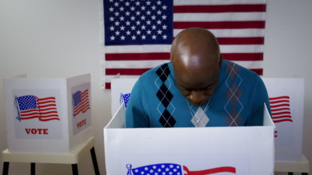 Front view African American man enters booth at polling station 4K video
