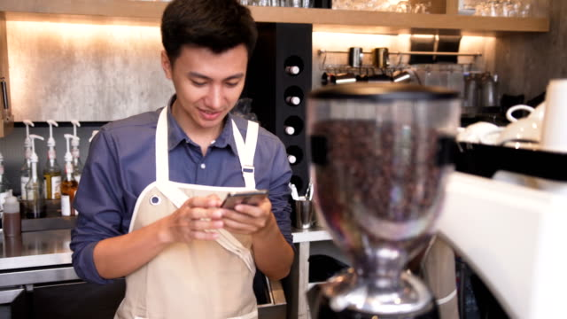 front view: Asian barista man is using the smartphone front view: Asian barista man is using the smartphone The technology is used to control and organize the small business. It is help owner to manage. small business saturday stock videos & royalty-free footage