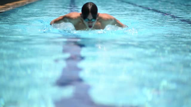 Front view Asian Chinese athlete swimmer swimming in swimming pool