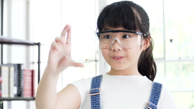 front view: Asian girl consider on petri dish with feeling exciting