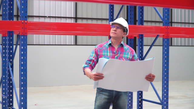 front view: Asian man engineer looking at blueprint for checking shelf and building in Warehouse