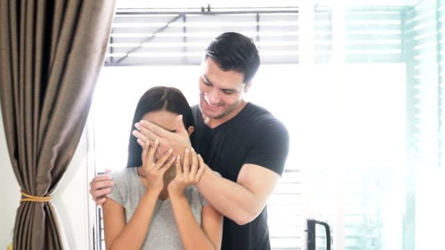 vista frontal: pareja joven atractiva está en movimiento, en una casa vacía. Hombre está cubriendo sus ojos de mujer para una sorpresa - vídeo