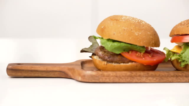 front view by dolly shot: cheeseburger and burger - cheeseburger filmów i materiałów b-roll