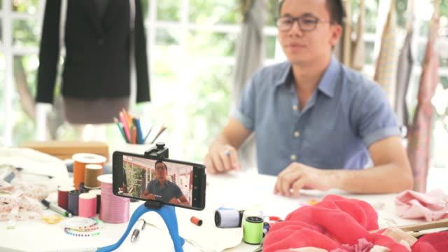 frontansicht von dolly erschossen: männliche mode-designer tun, video-streaming auf seinem smartphone - live ereignis stock-videos und b-roll-filmmaterial