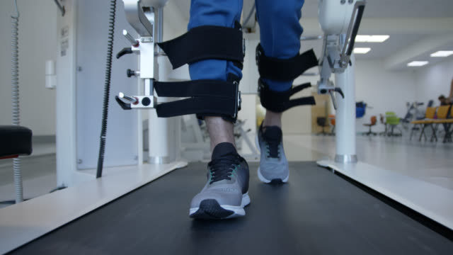 Front view close up of man walking with the help of a exoskeleton robot on treadmill