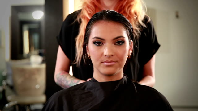 Front view closeup of beautiful young woman in a hair salon Closeup of beautiful young woman looking forward as her hair stylist capes and prepares her for a haircut cape garment stock videos & royalty-free footage