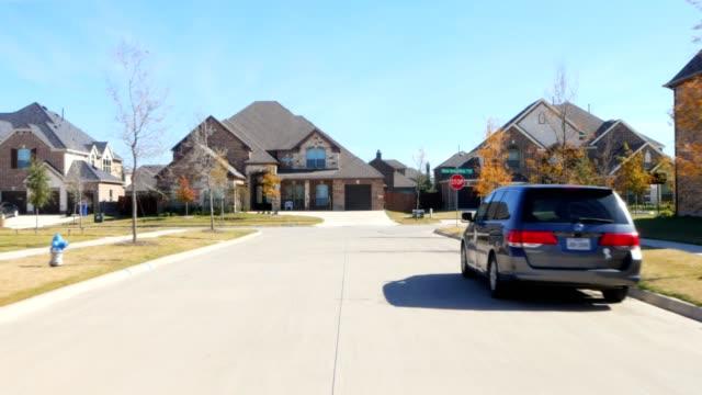 frontblick fahren durch wohnhäuser in suburban estate street - blickwinkel aufnahme stock-videos und b-roll-filmmaterial