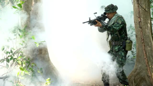 vidéos et rushes de vue de face: visage du groupe entièrement équipé et soldat armé paraît brume forme alors qu'il patrouillait dans la forêt tropicale - mitrailleuse