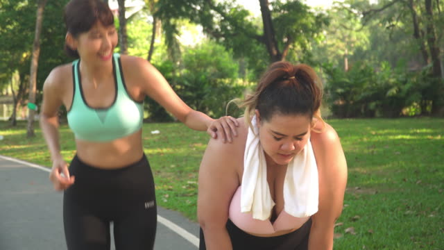 front view: female large build athlete so tried but her friend is coming to give the passion in a public park - trentenne video stock e b–roll