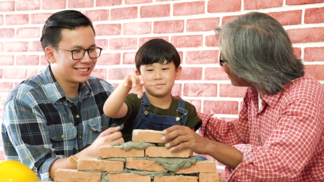 front view: grandfather, father and son lay brick on a new house together