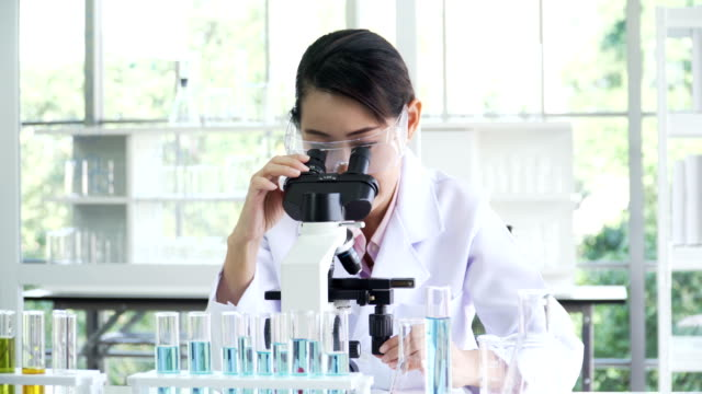 front view: Mid female Japanese scientist doing her research on optical microscope
