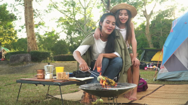 front view: Mother and daugther spend weekend time having picnic together and cooking BBQ