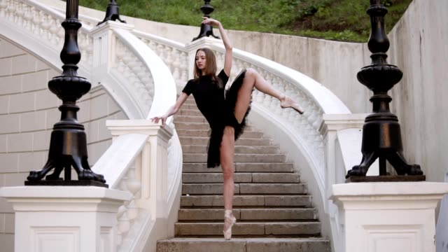 Front view of a graceful ballet movements. Young, blonde haired ballerina doing vertical twine and posing standing on a beginning of street stairs in black tutu. Daytime. Slow motion Front view of a graceful ballet movements. Young, blonde haired ballerina doing vertical twine and posing standing on a beginning of street stairs in black tutu. Daytime. Slow motion. doing the splits stock videos & royalty-free footage