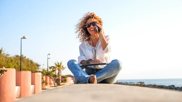 front view of a pretty young woman with curly hair, talking at the phone at the beach,with laptop for outdoor work - 40 44 lata filmów i materiałów b-roll
