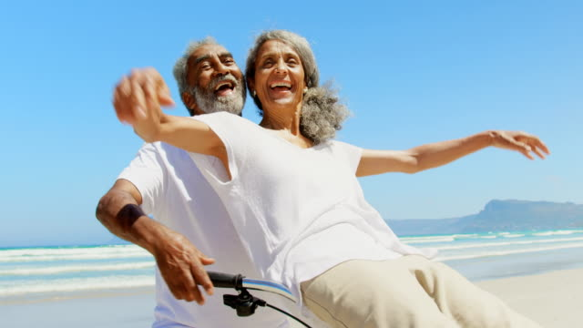 Front view of active senior African American woman sitting on man bicycle handlebars at beach 4k Front view of active senior African American woman sitting on man bicycle handlebars at beach. They are smiling and hand stretched out 4k mixed race person stock videos & royalty-free footage