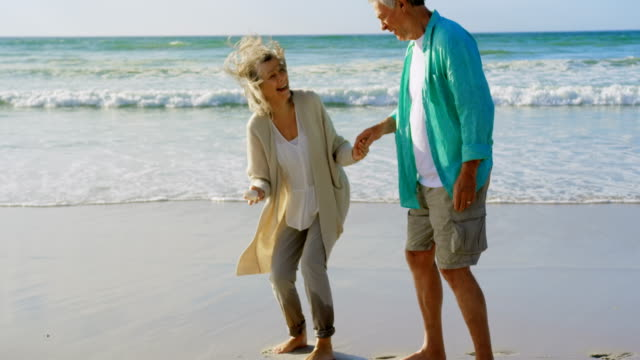 Front view of active senior Caucasian couple holding a seashell on the beach 4k