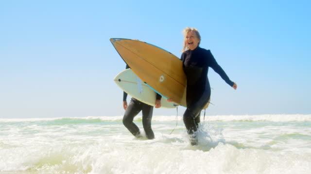 Frontansicht des aktiven, urkaukasischen Ehepaares, das am Strand 4k auf dem Meer läuft – Video