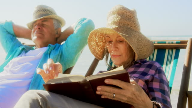 Front view of active senior Caucasian woman reading a book on the beach 4k