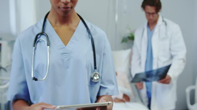 Frontansicht der afroamerikanischen Ärztin mit digitaler Tablette in der Station im Krankenhaus 4k – Video