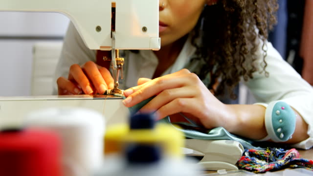front view of african american female fashion designer working with sewing machine in workshop 4k - sarta video stock e b–roll