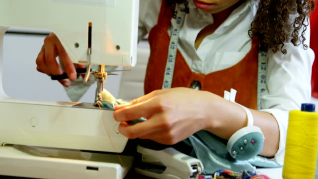 front view of african american female fashion designer working with sewing machine in workshop 4k - cucire video stock e b–roll