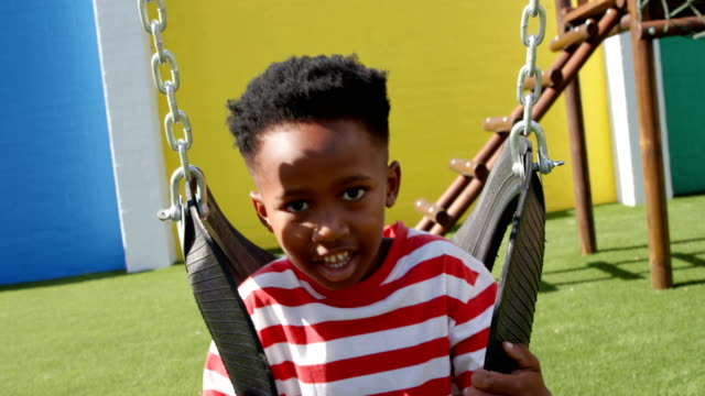 front view of african american schoolboy playing on a swing in school playground 4k - невинность стоковые видео и кадры b-roll