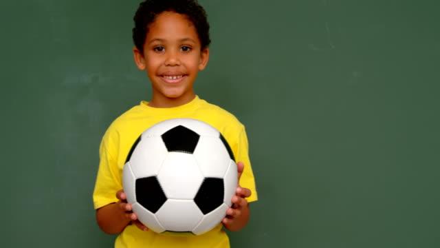 vidéos et rushes de vue de face de l'écolier d'afro-américain restant avec le football contre le tableau noir dans la salle de classe 4k - pureté