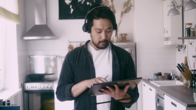 front bild av en asiatisk man använder digital tablet under telefonkonferens - 35 39 år bildbanksvideor och videomaterial från bakom kulisserna