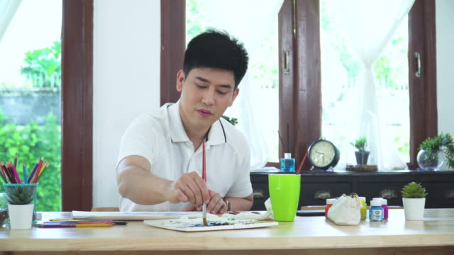 front view of Asian handsome man painting one paper page with watercolor to create artist skill and imagination and watercolor paint and equipment such as paintbrush and part.  Concept of young adult and leisure activity at the weekend.