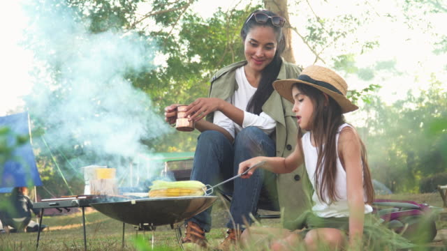 front view of Asian mother and mixed-race daughter travel camping together in a forest, Happy and relaxed woman and teenage girl cooking BBQ is in front of a tent. Concept of adventure family at the weekend.