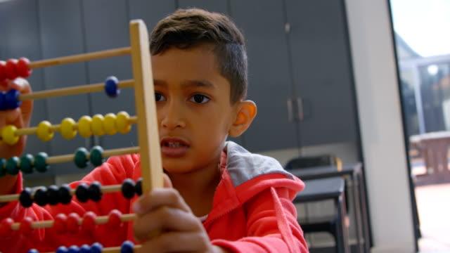 framifrån asiatiska skolpojke lösa matematiska problem med abacus på skriv bordet i ett klass rum i skolan 4k - abakus bildbanksvideor och videomaterial från bakom kulisserna