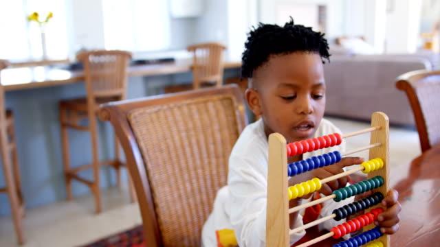 framsida av svart pojke leker med abacus på bekväma hem 4k - abakus bildbanksvideor och videomaterial från bakom kulisserna