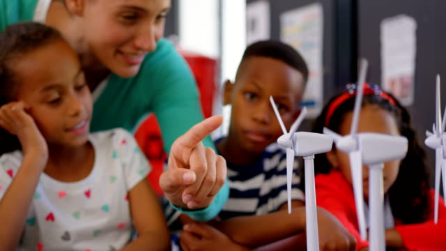 Front view of Caucasian female teacher teaching student about windmill in the classroom 4k