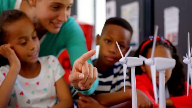 Frontansicht der kaukasischen Lehrerin, die Schülerin über Windmühle im Klassenzimmer 4k unterrichtet – Video