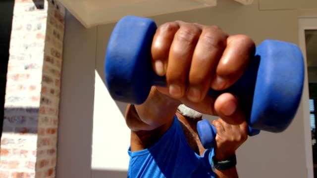 vídeos y material grabado en eventos de stock de vista frontal del hombre negro maduro determinado ejercicio y mirando a cámara en el patio trasero de casa 4k - puñetazo