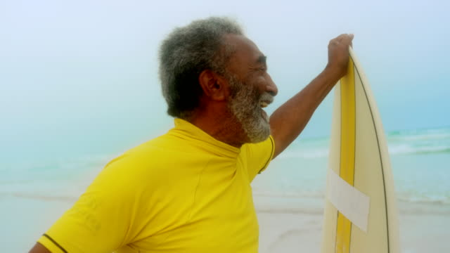 Front view of happy active senior African American man with surfboard standing on the beach 4k